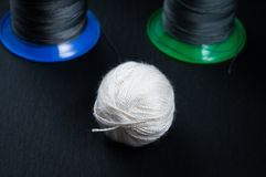 A ball of white thread and babin with gray thread for a sewing machine on a stone background royalty free stock images