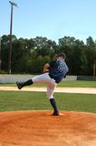 Ball Windup. Pitcher winds up for the pitch.  Young man has on navy and white uniform and is leaning back on one leg for the throw Royalty Free Stock Images