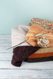 Ball of wool, needles and woolen sweater with spokes for handmade knitting in basket on wooden table. Stock Photography