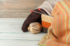 Ball of wool, needles and woolen sweater with spokes for handmade knitting in basket on wooden table. Stock Photo