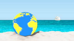 Ball with a world map pattern on a sandy beach with a blurred background. Stock Image
