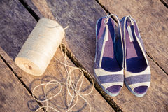 A ball of yarn around women sandals, shoes outdoors. A Royalty Free Stock Photo