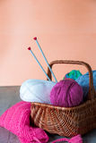 Ball of yarn and knitting needles in basket on a wooden grey table. Handmade. Stock Photography