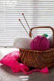 Ball of yarn and knitting needles in basket on a wooden grey table with window light. Close up. Handmade. Royalty Free Stock Photos