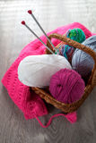 Ball of yarn and knitting needles in basket on a wooden grey table with window light. Close up. Top view. Handmade. Stock Images