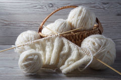 Ball of yarn and knitting on a table. Ball of yarn and knitting on a wooden table Royalty Free Stock Photography