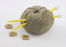 Ball Of Yarn and Two Yellow Needles. Ball of olive-colored yarn and two yellow knitting needles royalty free stock image