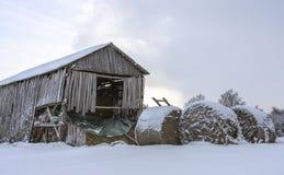 Balla rotonda di paglia sotto la neve sui precedenti di una tettoia di legno deformata immagine stock libera da diritti