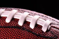 Ballabschluß des amerikanischen Fußballs oben auf schwarzem Hintergrund Stockbilder