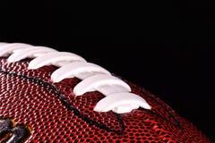 Ballabschluß des amerikanischen Fußballs oben auf schwarzem Hintergrund Stockbild