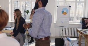Ballare biondo della donna di affari di bello divertimento felice, celebrante successo con i colleghi all'ufficio multietnico mod archivi video