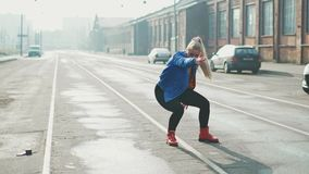 Ballare biondo della donna esegue il ballo hip-hop moderno che posa, stile libero in via, urbana metraggio delle azione 4k stock footage