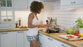 Ballare di modello adorabile felicemente mentre cucinando stock footage