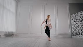 Ballare di pratica della ragazza bionda flessibile dell'interno di uno studio stock footage