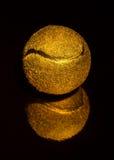 Balle de tennis chère d'or de cadeau sur un noir Photos stock