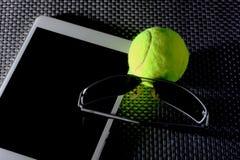Balle de tennis créative d'ensemble, tablette et lunettes de soleil noires, plan rapproché, sur le fond en métal Photographie stock