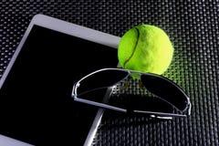 Balle de tennis créative d'ensemble, tablette et lunettes de soleil noires, plan rapproché, sur le fond en métal Images stock