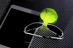 Balle de tennis créative d'ensemble, tablette et lunettes de soleil noires, plan rapproché, sur le fond en métal Photo libre de droits