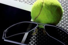 Balle de tennis créative d'ensemble, tablette et lunettes de soleil noires, plan rapproché, sur le fond en métal Photos libres de droits