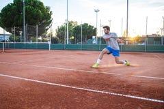 Balle de tennis de portion d'homme sur le coucher du soleil Photos libres de droits