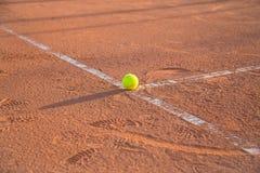 Balle de tennis se trouvant sur la ligne blanche sur le court de tennis Images stock