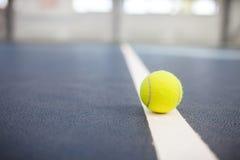Balle de tennis sur la fin de cour avec la pièce photographie stock