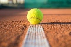 Balle de tennis sur la ligne blanche un jour ensoleillé Images stock