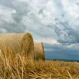 Balle della paglia sulle nuvole di tempesta del terreno coltivabile Fotografia Stock