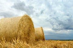 Balle della paglia sulle nuvole di tempesta del terreno coltivabile Immagine Stock Libera da Diritti