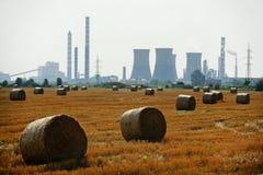 Balle di fieno con la centrale petrolchimica su fondo Fotografia Stock Libera da Diritti