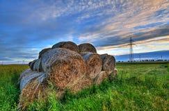 Balle di fieno in un campo al tramonto Fotografie Stock Libere da Diritti