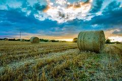 Balle di paglia sul campo irlandese al tramonto Fotografia Stock Libera da Diritti