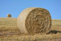 Balle di una paglia e una palla del fieno nell'orizzonte sul campo raccolto Immagini Stock Libere da Diritti