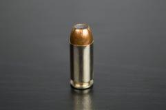 Balle simple pour une arme à feu sur une table noire Image stock