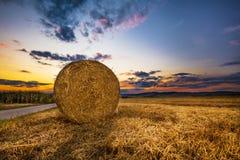 Ballen Heu auf dem Feld und dem Sonnenuntergang stockbilder