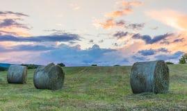Ballen Heu auf Rollenhügel bei Sonnenuntergang Stockfotografie