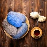 Ballen van grijze en blauwe draden in een plaat, een kop thee op een schotel en breinaalden op een houten achtergrond royalty-vrije stock foto