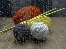 Ballen van het breien van wol met breinaalden op een houten die lijst, door een regenachtig venster worden gezien royalty-vrije stock foto