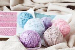 Ballen van roze en grijs garen, gebreide stof op een wollen backgrou Stock Foto