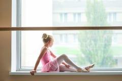 Balleria novo que senta-se no peitoril da janela Foto de Stock Royalty Free