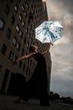 Ballerina με την ομπρέλα στην οδό πόλεων στον ουρανό και το bui υποβάθρου Στοκ Εικόνα