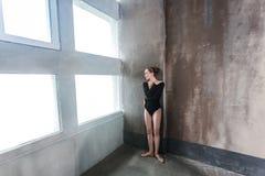Ballerina που περιμένει κοντά στο παράθυρο, αγκάλιασμα ο ίδιος και κοιτάζοντας μακριά στοκ φωτογραφία με δικαίωμα ελεύθερης χρήσης