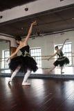 Ballerina πρόβας στην αίθουσα Άσπροι τοίχοι, σκοτεινό ξύλινο πάτωμα, σκοτεινό ανώτατο όριο, όμορφοι πολυέλαιοι, Η αντανάκλαση στοκ φωτογραφίες με δικαίωμα ελεύθερης χρήσης