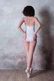 Ballerina σε ένα άσπρο κοστούμι λουσίματος με ένα όμορφο σώμα που στέκεται στα παπούτσια pointe Στοκ Φωτογραφίες
