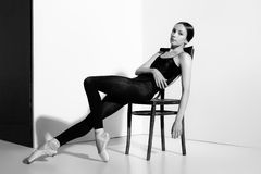 Ballerina στη μαύρη τοποθέτηση εξαρτήσεων σε μια ξύλινη καρέκλα, υπόβαθρο στούντιο Στοκ Φωτογραφία