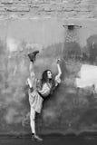 Ballerina στο κοντό φόρεμα και μπότες κοντά σε έναν συμπαγή τοίχο Στοκ εικόνες με δικαίωμα ελεύθερης χρήσης