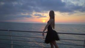 Ballerina χορού στο μαύρο tutu μπαλέτου και pointe στο ανάχωμα επάνω από τον ωκεανό ή θάλασσα στην ανατολή ή το ηλιοβασίλεμα Νέος απόθεμα βίντεο