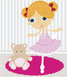 Ballerina. Girl doing a ballet pose in room, teddy bear sitting on the floor Royalty Free Stock Photos