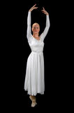 Ballerina. With arms raised dressed in fancy white gown isolated over a black background Royalty Free Stock Photography