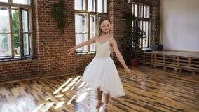 Ballerina affascinante graziosa in tutu bianco eseguire ballo classico alla scuola di balletto Giovane ballerina esile in vestito video d archivio